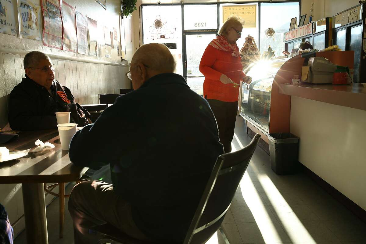 From right: Astrid Rivera orders an apple fritter as Ed Raffo and Vern Alonzo chat at the table at Donut Time on Tuesday, Dec. 20, 2016 in Pacifica, Calif. The longtime donut shop, located at 1235 Linda Mar Shopping Center, is set to lose its lease and close in January. Rivera, of San Francisco, is a regular customer who visits the shop 2-3 times per week for the last three years. Raffo and Alonzo, both of Pacifica and retired military veterans, said they've visited the donut shop almost every day for more than 25 years.