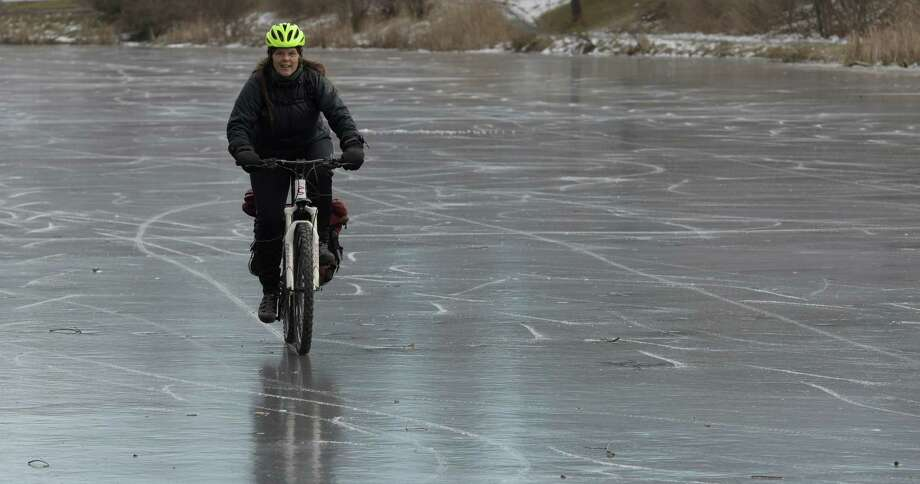 Claire Nolan tires out her studded tire on her bike on Buckingham Lake which opened today without least 7 inches of ice according to Albany DGS Tuesday Dec. 20, 2016 in Albany, N. Y  (Skip Dickstein/Times Union) Photo: SKIP DICKSTEIN