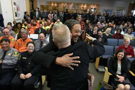 Alameda County District One Supervisor Scott Haggerty, left, gives a hug  and an award to Dean Chambers of Alameda Health Care Services as the Alameda County Board of Supervisors honored first responders to the Ghost Ship fire at the Alameda County Administration building in Oakland, CA, on Tuesday, December 20, 2016.