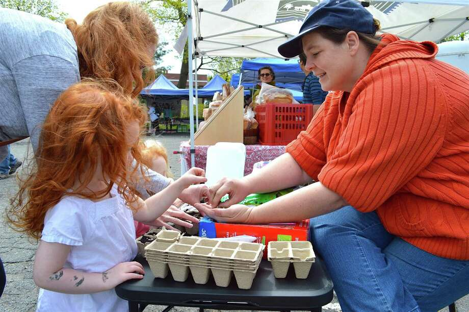 Lexi Gazy, market master of the New Canaan Farmer's Market, talks to Caroline Rossi, 4, of Norwalk, about how to plant peas at the 2016 Farmers Market. Photo: Jarret Liotta / Hearst Connecticut Media / New Canaan News  freelance