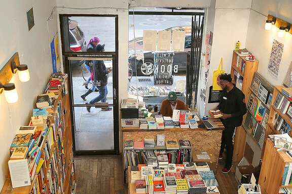 Overview of E.M. Wolfman General Interest Small Bookstore with writer, director, and curator Christian Johnson (right) on Monday, December 19, 2016, in Oakland, Calif.