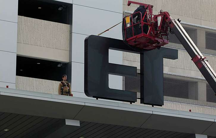 Workers affix a Metro logo to the front of the new Grand Parkway Park and Ride garage near Interstate 10 on Dec. 20. The 1,650-space garage is expected to open in February.