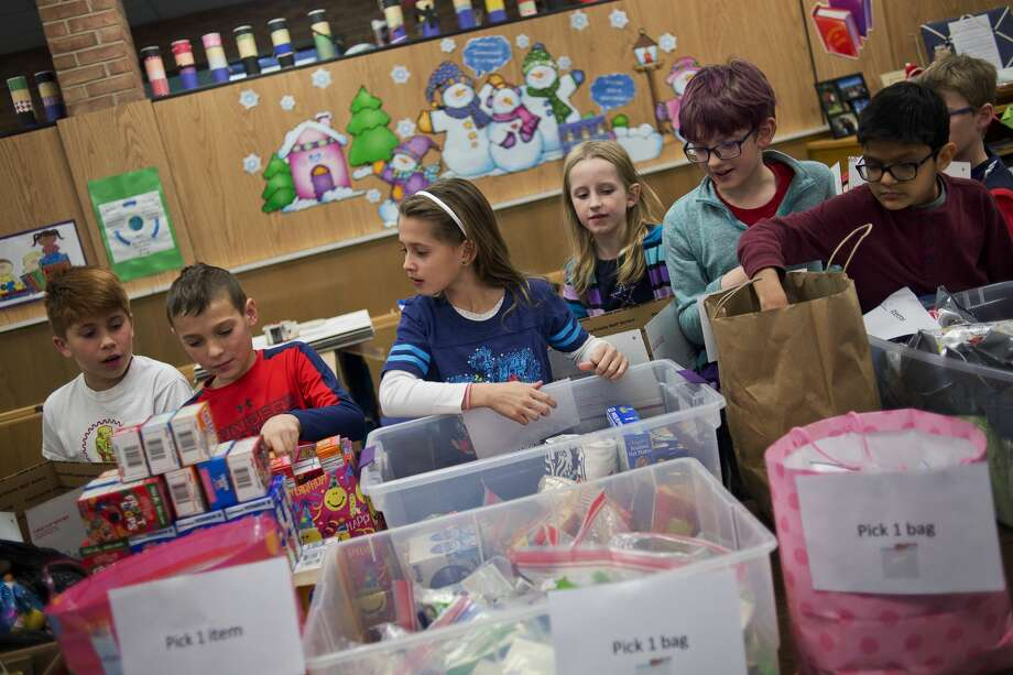 Students compile care packages on Tuesday at Adams Elementary. During their holiday party, Cari Marchand's 4th grade class assembled 31 care packages for soldiers complete with original poems and letters of gratitude. The class partnered with local nonprofit Aaron's Gifts from Home which was founded by Deb Ullom to honor her son Aaron, a Navy Corpsman who was killed in action in 2011 while saving a Marine in Afghanistan. Photo: Erin Kirkland/Midland Daily News