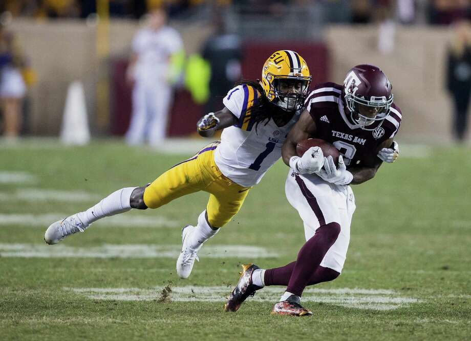 Speedy Noil (right) of the Texas A&M Aggies makes a catch as Donte Jackson of the LSU Tigers makes the tackle in the second half at Kyle Field on Nov. 24, 2016 in College Station. Photo: Bob Levey /Getty Images / 2016 Getty Images