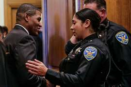 William Scott (left), a veteran Los Angeles deputy chief, chats with police officers after press conference which announced Scott as the new San Francisco police chief at City Hall, in San Francisco, Calif., on Tuesday, Dec. 20, 2016.