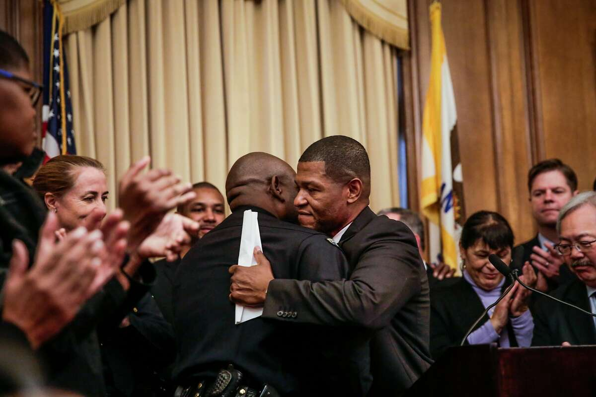 William Scott (left), a veteran Los Angeles deputy chief, hugs the interim police chief Tony Chaplin (left) during a press conference which announced Scott as the new San Francisco police chief at City Hall, in San Francisco, Calif., on Tuesday, Dec. 20, 2016.