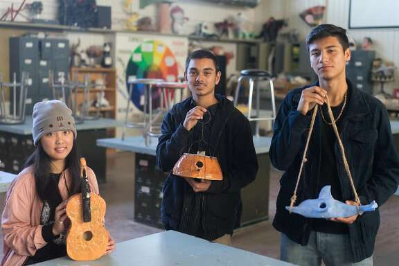 Left to right, Charissa Garcia, Arnold Seng and Victor Medina pose for a photograph at Mt. Eden High School in Hayward, Calif. on Tuesday, Dec. 20, 2016. Students at two high schools have built birdhouses to auction off in January to see who will raise the most money.