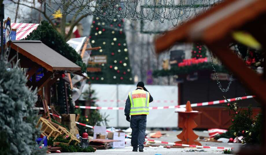 A policeman surveys the destruction at the Christmas market near the Kaiser Wilhelm Memorial Church on Tuesday, the day after a truck attack killed 12 people. The search continues for the attacker after an initial suspect was released for lack of evidence. Photo: TOBIAS SCHWARZ, Staff / AFP or licensors