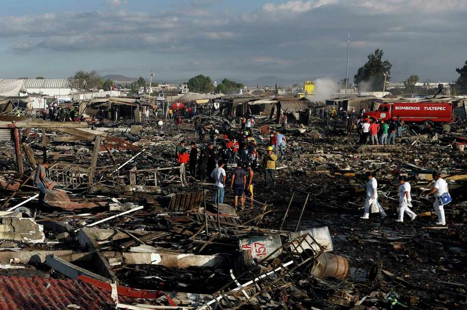 Firefighters and rescue workers walk through the scorched ground of Mexico's best-known fireworks market after an explosion explosion ripped through it, inTultepec, Mexico, Tuesday, Dec. 20, 2016. National Civil Protection Coordinator Luis Felipe Puente told Milenio TV that dozens were hurt but he had no immediate report of any fatalities at the open-air San Pablito Market in Tultepec, in the State of Mexico. Photo: Eduardo Verdugo, AP / AP