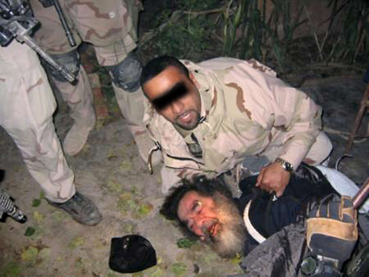 This unsourced picture allegedly shows ousted Iraqi leader Saddam Hussein being dragged out of his hiding following his capture by US troops 13 December 2003 in an underground hole at a farm in the village of ad-Dawr, near his hometown of Tikrit in northern Iraq.  AFP PHOTO/HO (Photo credit should read /AFP/Getty Images)