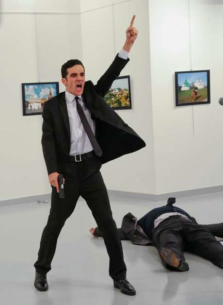 FILE - In this Monday, Dec. 19, 2016 file photo, Mevlut Mert Altintas shouts after shooting Andrei Karlov, right, the Russian ambassador to Turkey, at an art gallery in Ankara, Turkey. At first, AP photographer Burhan Ozbilici thought it was a theatrical stunt when a man in a dark suit and tie pulled out a gun during the photography exhibition. The man then opened fire, killing Karlov. (AP Photo/Burhan Ozbilici) Photo: Burhan Ozbilici, STF / Copyright 2016 The Associated Press. All rights reserved.