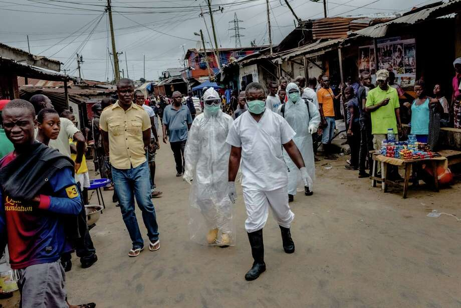 Workers from an Ebola isolation ward walk to the body of a suspected victim of the disease in a neighborhood of Monrovia, Liberia, in August 2014. Advocates for the poor, health experts and government officials don't know what direction the incoming Trump administration is going to take when it comes to global health aid. Photo: DANIEL BEREHULAK, STR / NYTNS