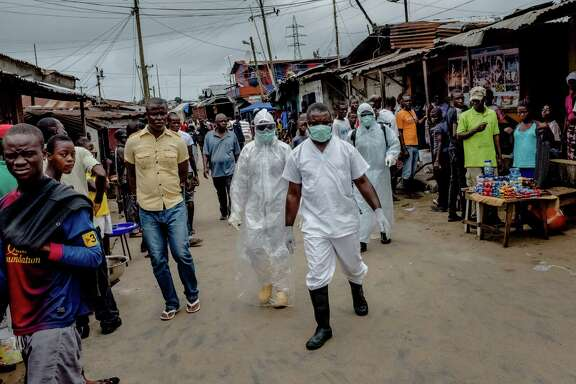 Workers from an Ebola isolation ward walk to the body of a suspected victim of the disease in a neighborhood of Monrovia, Liberia, in August 2014. Advocates for the poor, health experts and government officials don't know what direction the incoming Trump administration is going to take when it comes to global health aid.