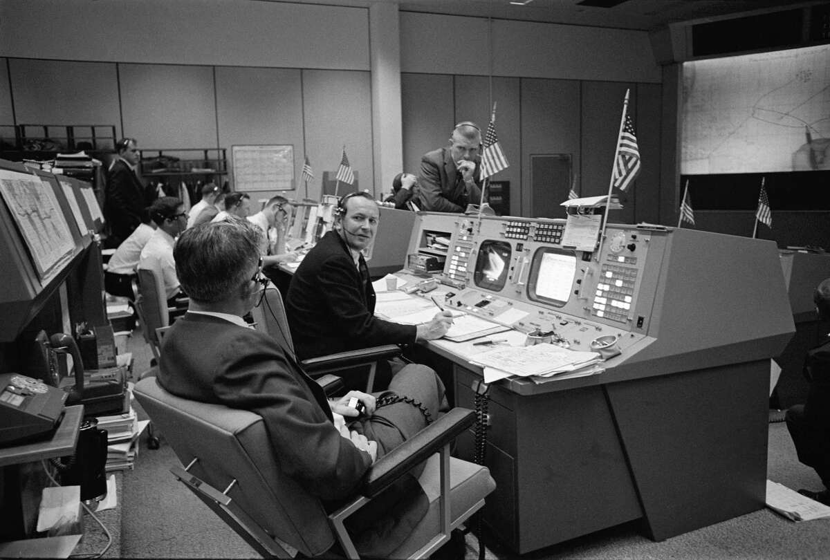 John D. Hodge left, Christopher C. Kraft Jr. and Eugene F. Kranz discuss recovery operations for the Gemini-6 spacecraft in the Mission Control on Dec. 16, 1965. (NASA Photo)