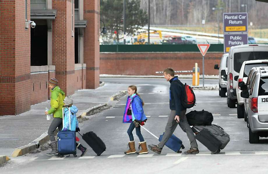 A family crosses the road in front of the terminal after arriving at the Albany International Airport on Tuesday, Dec. 20, 2016 in Colonie, N.Y. (Lori Van Buren / Times Union) Photo: Lori Van Buren / 20039201A