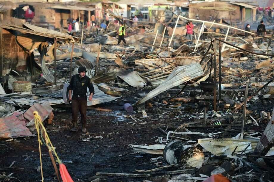 Firefighters work amid the debris left by the deadly blast that occurred in a fireworks market Tuesday on the northern outskirts of Mexico City. Most of the fireworks stalls were leveled. Photo: RONALDO SCHEMIDT, Staff / AFP or licensors