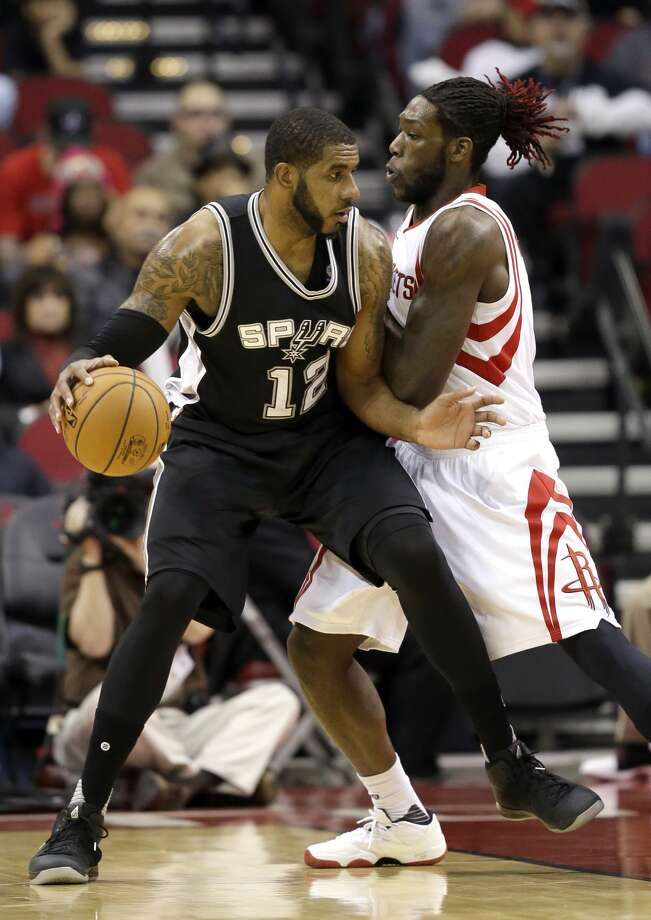 San Antonio Spurs' LaMarcus Aldridge (12) is guarded by Houston Rockets' Montrezl Harrell during the first half of an NBA basketball game Tuesday, Dec. 20, 2016, in Houston. (AP Photo/David J. Phillip) Photo: David J. Phillip/Associated Press