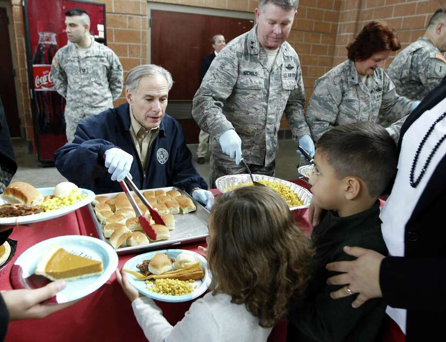 Texas Gov. Greg Abbott, left, hands out rolls to Oliver and Julieta Loperena during an early Christmas celebration with members members of the Texas National Guard, who are deployed on the border of Mexico, and their families, Tuesday, Dec. 20, 2016 in Weslaco, Texas. (Nathan Lambrecht/The Monitor via AP) Photo: Nathan Lambrecht, MBI / Associated Press / The Monitor