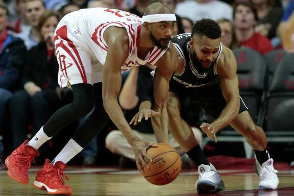 Houston Rockets forward Corey Brewer (33) takes a loose ball on the floor away from San Antonio Spurs guard Patty Mills (8) during the second quarter of an NBA basketball game at Toyota Center on Tuesday, Dec. 20, 2016, in Houston.