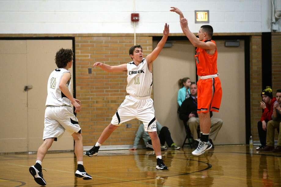 Bullock Creek's Josh Zastrow reaches up to block Alma's Brec Alward on Tuesday at Bullock Creek High School. Photo: Erin Kirkland/Midland Daily News
