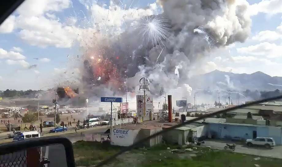 This image made from video recorded from a passing car shows an explosion ripping through the San Pablito fireworks' market in Tultepec, Mexico, Tuesday, Dec. 20, 2016. Sirens wailed and a heavy scent of gunpowder lingered in the air after the afternoon blast at the market, where most of the fireworks stalls were completely leveled. According to the Mexico state prosecutor there are at least 26 dead. (Jose Luis Tolentino via AP) Photo: Jose Luis Tolentino/AP