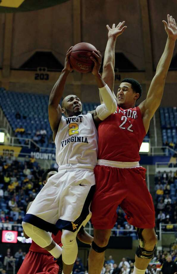 West Virginia guard Jevon Carter (2) drives to the basket as Radford forward Sterling Christy (22) attempts to block his shot during the first half of an NCAA college basketball game, Tuesday, Dec. 20, 2016, in Morgantown, W.Va. (AP Photo/Raymond Thompson) ORG XMIT: WVRT101 Photo: Ray Thompson / FR171247 AP