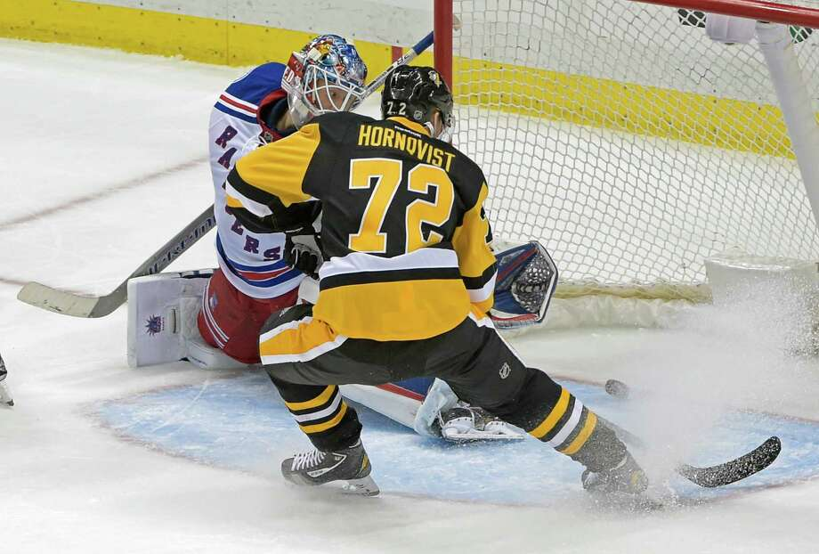 Pittsburgh Penguins right wing Patric Hornqvist (72) slides the puck past New York Rangers goalie Henrik Lundqvist (30) for a goal during the third period of an NHL hockey game Tuesday, Dec. 20, 2016, in Pittsburgh. (AP Photo/Fred Vuich) ORG XMIT: PAFV106 Photo: Fred Vuich / Fred Vuich