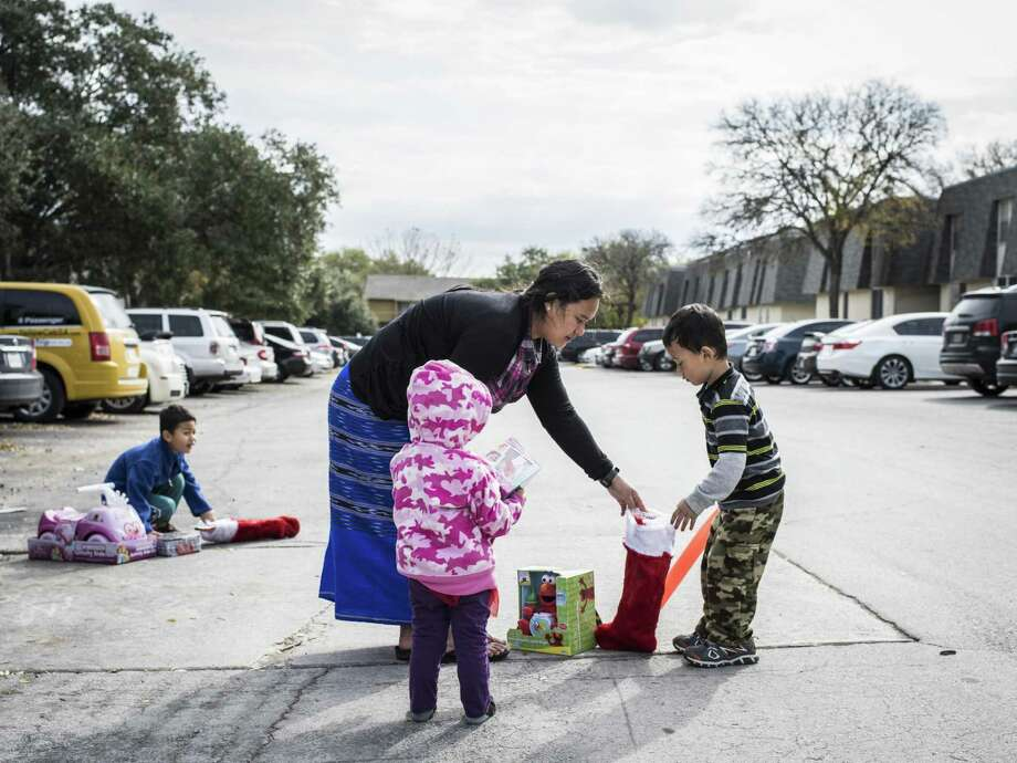 Soemeh helps her children Boe, 6, (left), Elizabeth, 2, (center), and Moriko, 4,  gather their toys during the fourth  toy giveaway for refugee children put on by the Bexar County Young Tejano Democrats in San Antonio on Sunday. Soemeh and her children are refugees from Burma. The group of volunteers went to various apartments where refugee families have settled in San Antonio. Photo: Matthew Busch /For The Express-News / © Matthew Busch