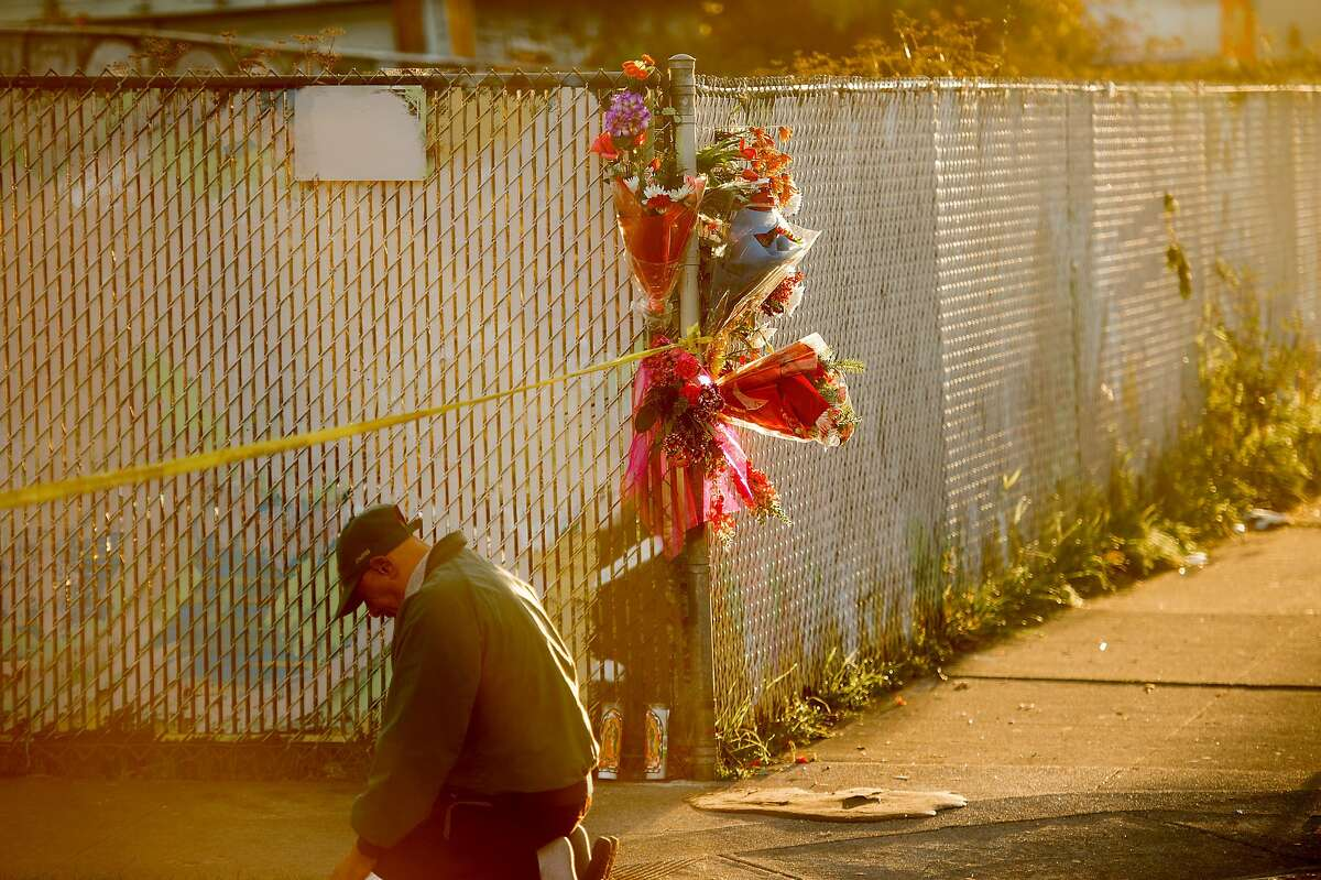 """Elijah Hope kneels at the scene of the Ghost Ship warehouse fire at sunrise on Sunday, Dec. 4, 2016, in Oakland, Calif. Hope, who lives nearby, said he was """"saying goodbye to the souls."""""""