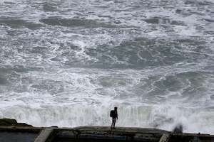 A man walks on a ledge of the old Sutro Baths in front of roiling surf in San Francisco, Calif. on Saturday, March 12, 2016 before rain was once again forecast to drench the Bay Area later in the afternoon.
