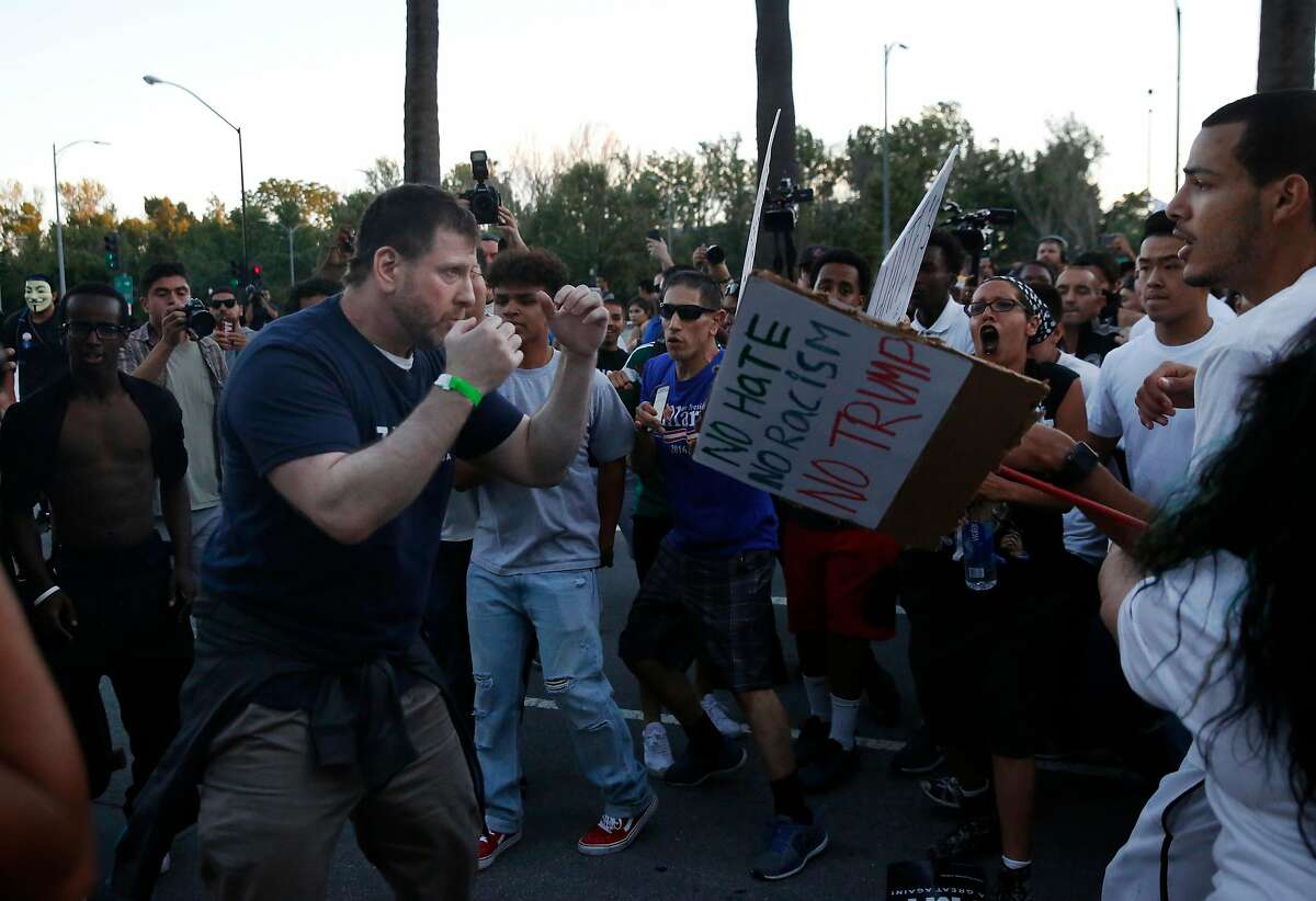 A Donald Trump supporter gets in a fighting position after getting in a tiff with anti-Trump protesters after they surrounded him and snatched his hat off of his head near the convention center where presidential candidate Donald Trump held a campaign rally June 2, 2016 in downtown San Jose, Calif.