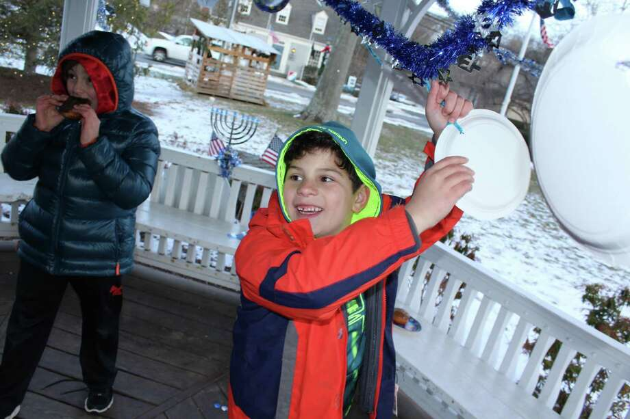 Josh Meltzer, 9, hangs up Hanukkah decorations around the gazebo at the Green in Wilton Town Center as his friend Gabe Conley, 10, looks on. Photo: Pat Tomlinson / Hearst Connecticut Media