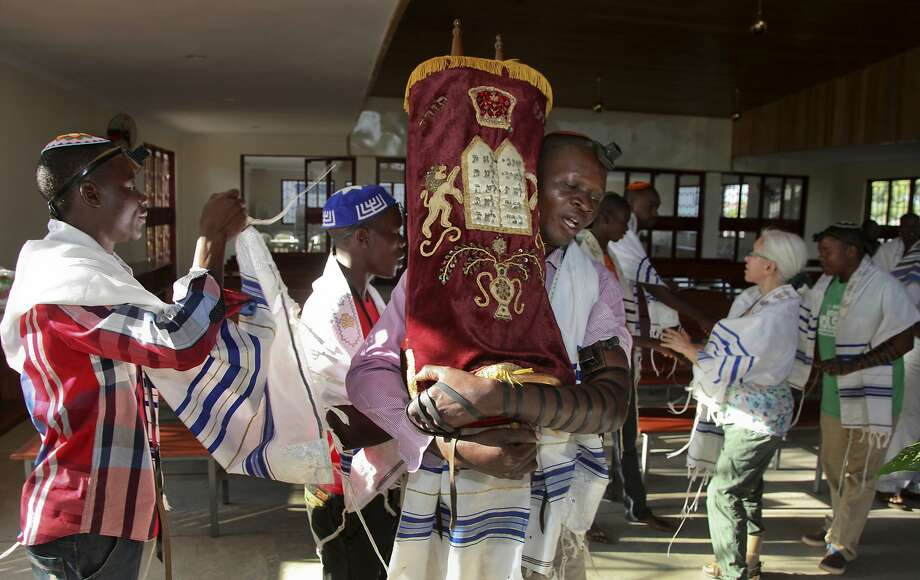 A Ugandan Jew carries the Torah during services at the new Stern Synagogue built largely with money donated by Americans in the eastern town of Mbale. Photo: Stephen Wandera, Associated Press