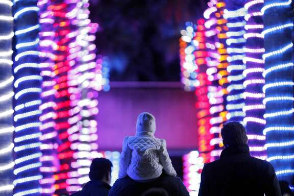 Lester Pineda carries his daughter Isla, 2, through a corridor of lighted palm trees during the Zoo Lights at the San Francisco Zoo in San Francisco, Calif., on Monday, December 19, 2016. The