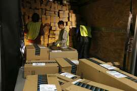 """Amazon.com employees pack up a shipping truck at an Amazon.com Fulfillment Center on """"Cyber Monday"""" on the busiest online shopping day of the holiday season Monday, Dec. 2, 2013, in Phoenix. (AP Photo/Ross D. Franklin)"""