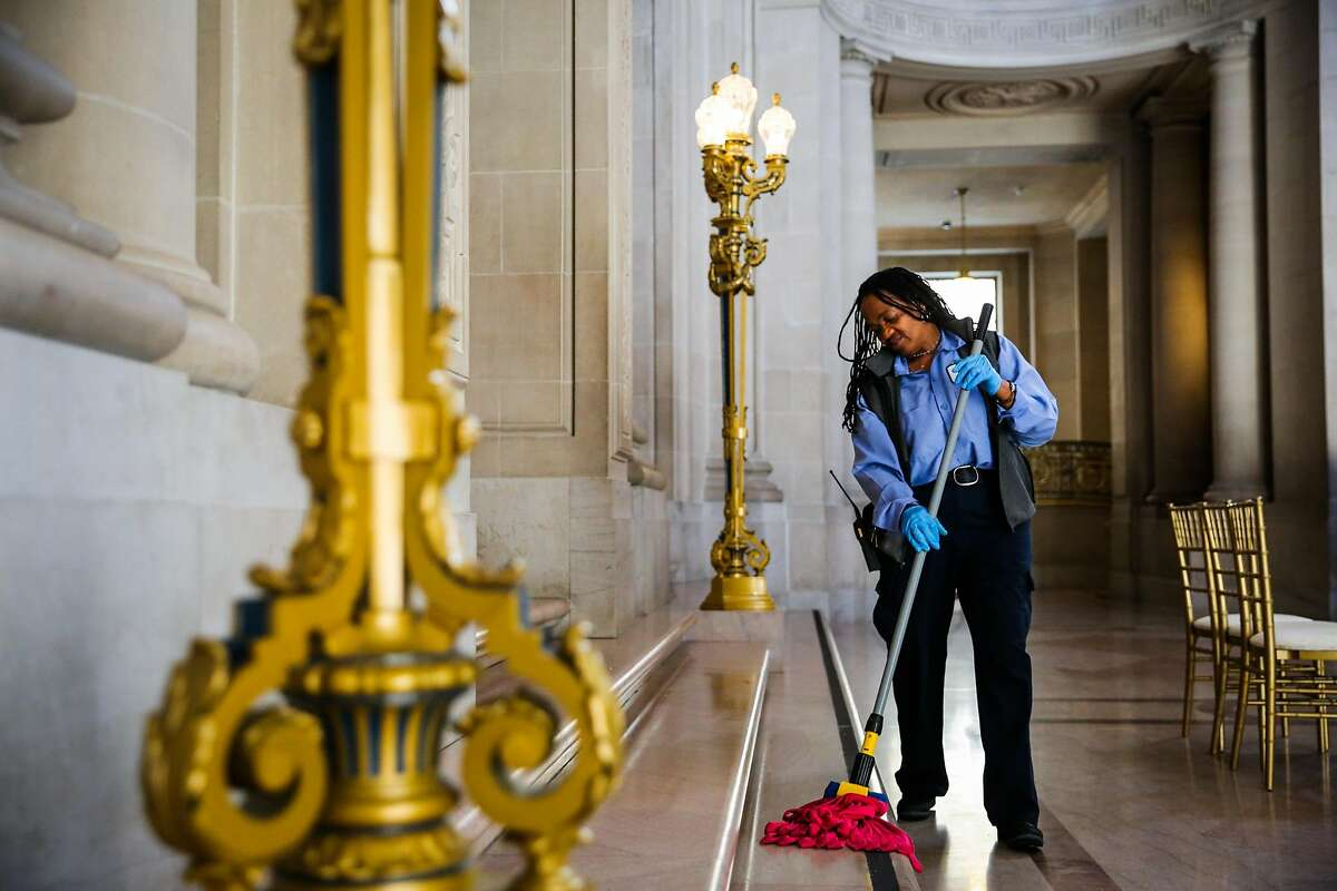 Claudine Bingham, a longtime maintenance worker at City Hall, mops the floor of a balcony at City Hall, in San Francisco, California, on Monday, Nov. 28, 2016. This past summer, via facebook, Claudine found her sister Barbara Barnette and they reunited for the first time in person in 45 years.