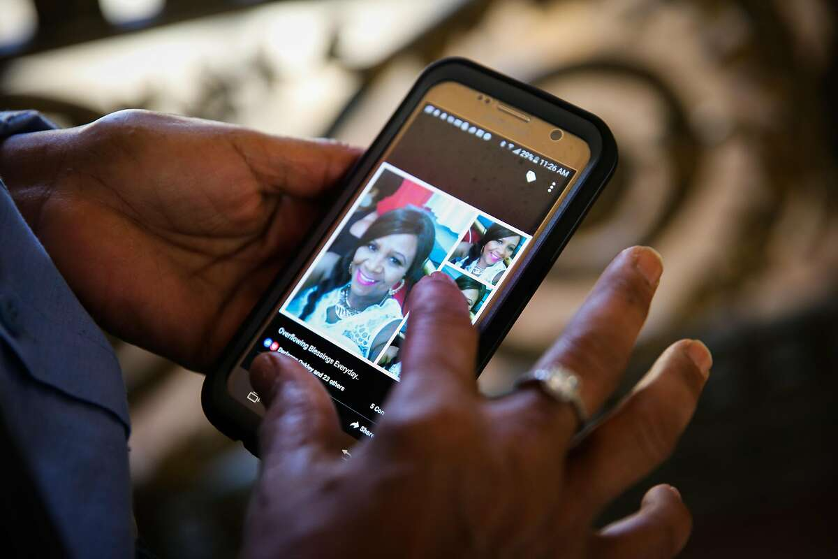 Claudine Bingham, a longtime maintenance worker at City Hall, looks at a photo of her sister Barbara Barnette on her phone, at City Hall in San Francisco, California, on Monday, Nov. 28, 2016. This past summer, via facebook, Claudine found her sister Barbara Barnette and they reunited for the first time in person in 45 years.