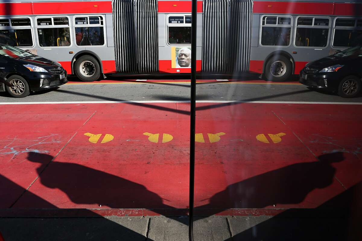 A bus using one of the red transit-only lanes and a car driving in the center of the lanes is seen reflected in a sign at 16th and Mission St on Friday, December 16 2016 in San Francisco, Calif.