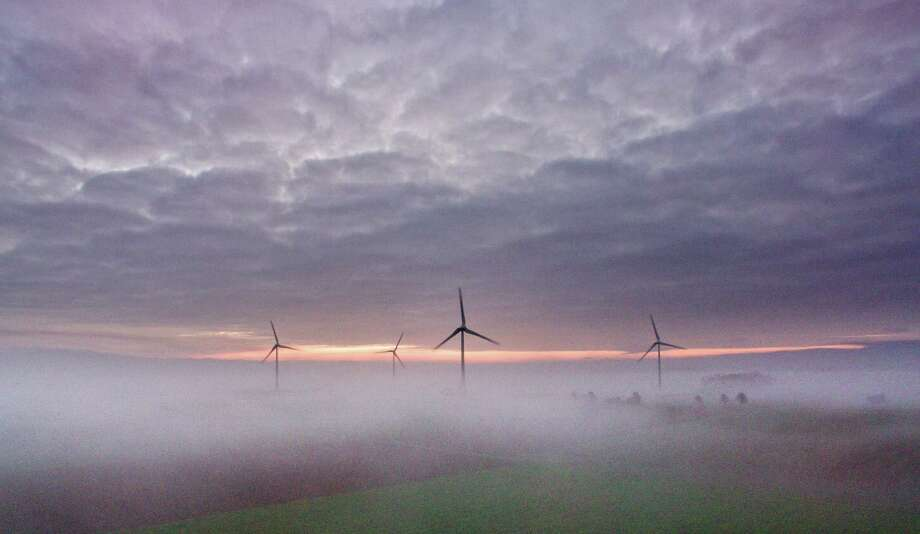 Wind turbines stand in a sea of  mist near Sehnde, Germany, early Monday Dec. 19,  2016. Weather forecasts predict changeable weather for Germany.  (Julian Stratenschulte/dpa via AP) Photo: Julian Stratenschulte, SUB / dpa