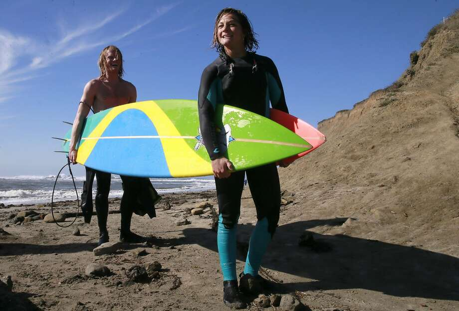 Dr.  Joseph Hardeman (left) and Bianca Valenti carry their boards to the car after surfing at Mavericks in Half Moon Bay. Photo: Michael Macor, The Chronicle