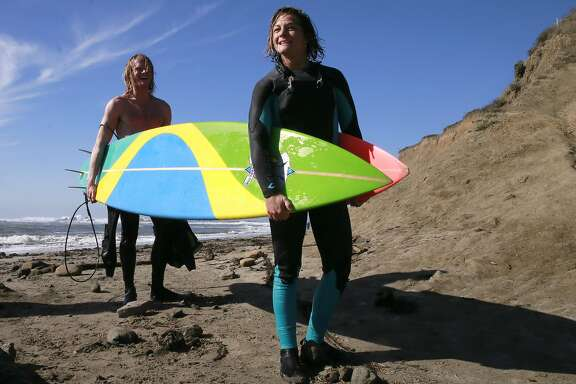 Dr. Joseph Hardeman and fellow surfer Bianca Valenti carry their surf boards to their car after spending the morning riding the Mavericks break in Half Moon Bay, California, on Friday November 4, 2016