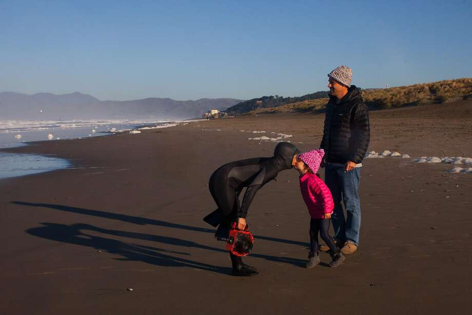 Sachi Cunningham, an assistant professor at S.F. State University, leans down to kiss daughter Nami, 4, after shooting the surf. Photo: Brian Feulner, Special To The Chronicle