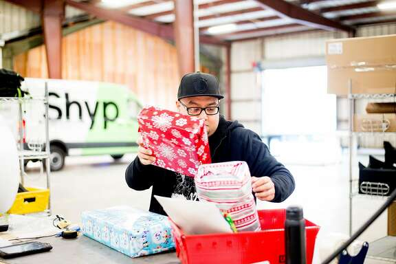 Senior packing technician Mike Hiquiana sorts gift-wrapped items at Shyp on Tuesday, Dec. 6, 2016, in San Francisco.