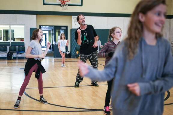 Buck Chavez, a PE teacher at San Geronimo Valley School, plays music and dances along with his students (left rot right) Eva Thomas, Beth Brisson, Kaitlyn Signor, and Grace Chavez (Buck's daughter) during a PE class on December 14, 2016 in San Geronimo, Calif.