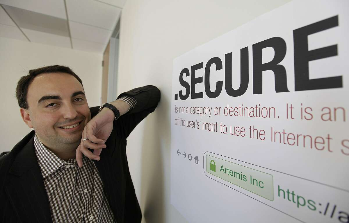 In this photo taken Friday, June 8, 2012 Alex Stamos CTO of Artemis Internet, an NCC Group Company, poses by a domain name poster at their offices in San Francisco. Some 2,000 proposals have been submitted as part of the largest expansion of the Internet address system since its creation in the 1980s. These suffixes would rival �.com� and about 250 others now in use. The organization behind it, the Internet Corporation for Assigned Names and Numbers, will announce a full list and other details in London on Wednesday. (AP Photo/Eric Risberg)