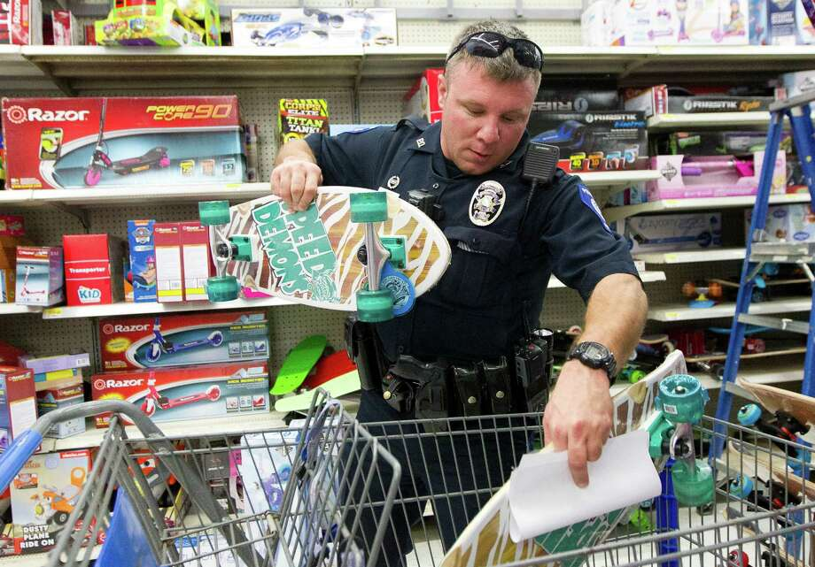 david peek patrol officer with the conroe police department places a pair of skateboards