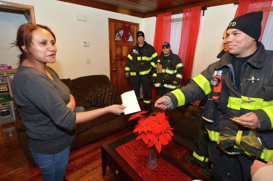 Firefighter George Baez presents gift cards on Wednesday December 21, 2016 to Yosely Lopez, the widow of Belarmino Lima who died earlier this year in Norwalk Conn. after being crushed in his driveway under a truck he was working on. Norwalk Firefighters are making a donations for food and services and toys for the childern to the Lima family, Photo: Alex Von Kleydorff / Hearst Connecticut Media / Connecticut Post