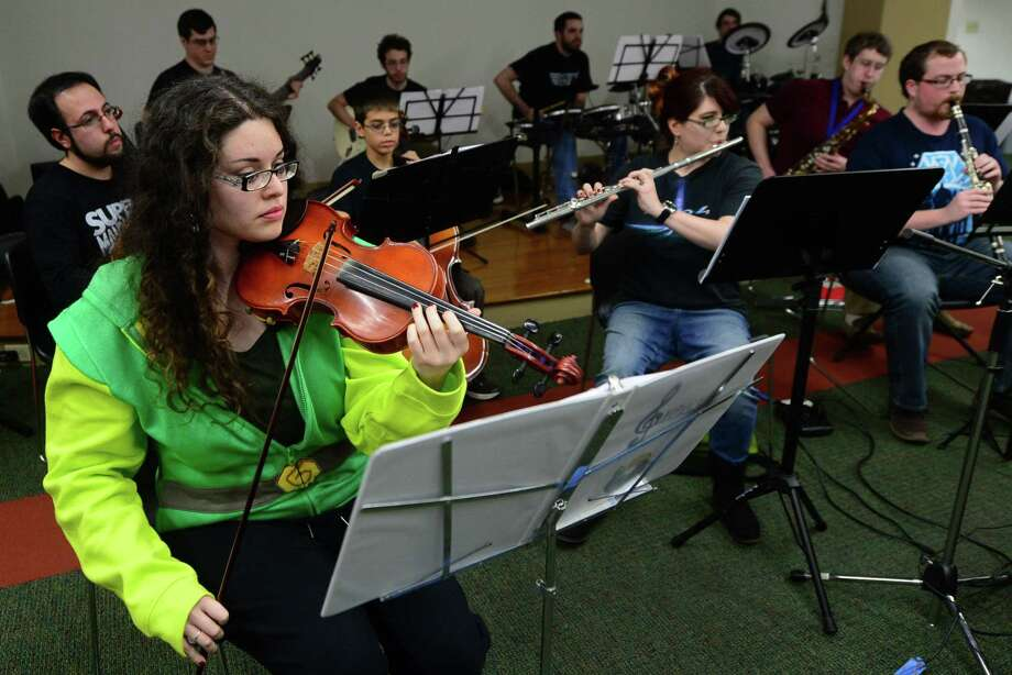 Cindy Reyes, left, and The National Gamers Symphony Orchestra (NGSO) play in their inaugural performance Saturday, December 3, 2016, at the South Norwalk Branch Library in Norwalk, Conn. NGSO was founded by Bryan Doyle, a former conductor for the University of Maryland's Gamer Symphony Orchestra. The small group of local musicians meet twice a month in an effort to improve as musicians, introduce the local community to the world of videogame music and promote musicianship. The group covered a few genres from the early days of video games to the modern: Starfox, The Legend of Zelda, and Journey. Photo: Erik Trautmann / Hearst Connecticut Media / Norwalk Hour