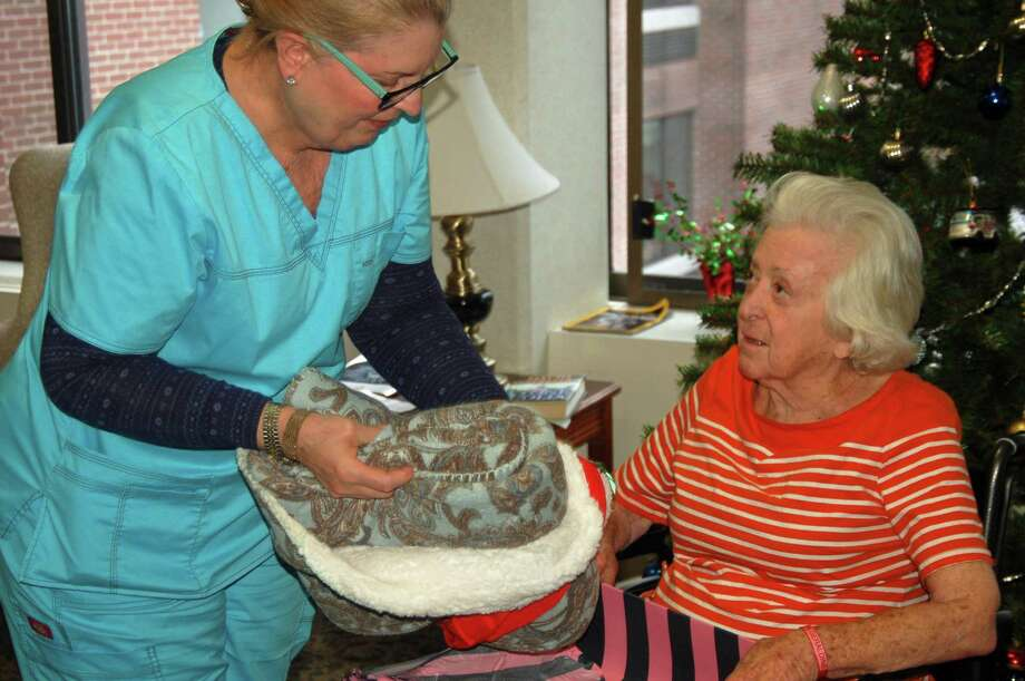 Cathy Sages, a patient care coordinator at The Nathaniel Witherell, helps long-term resident Geraldine Kalan with a Christmas gift of a warm blanket. Photo: Ken Borsuk