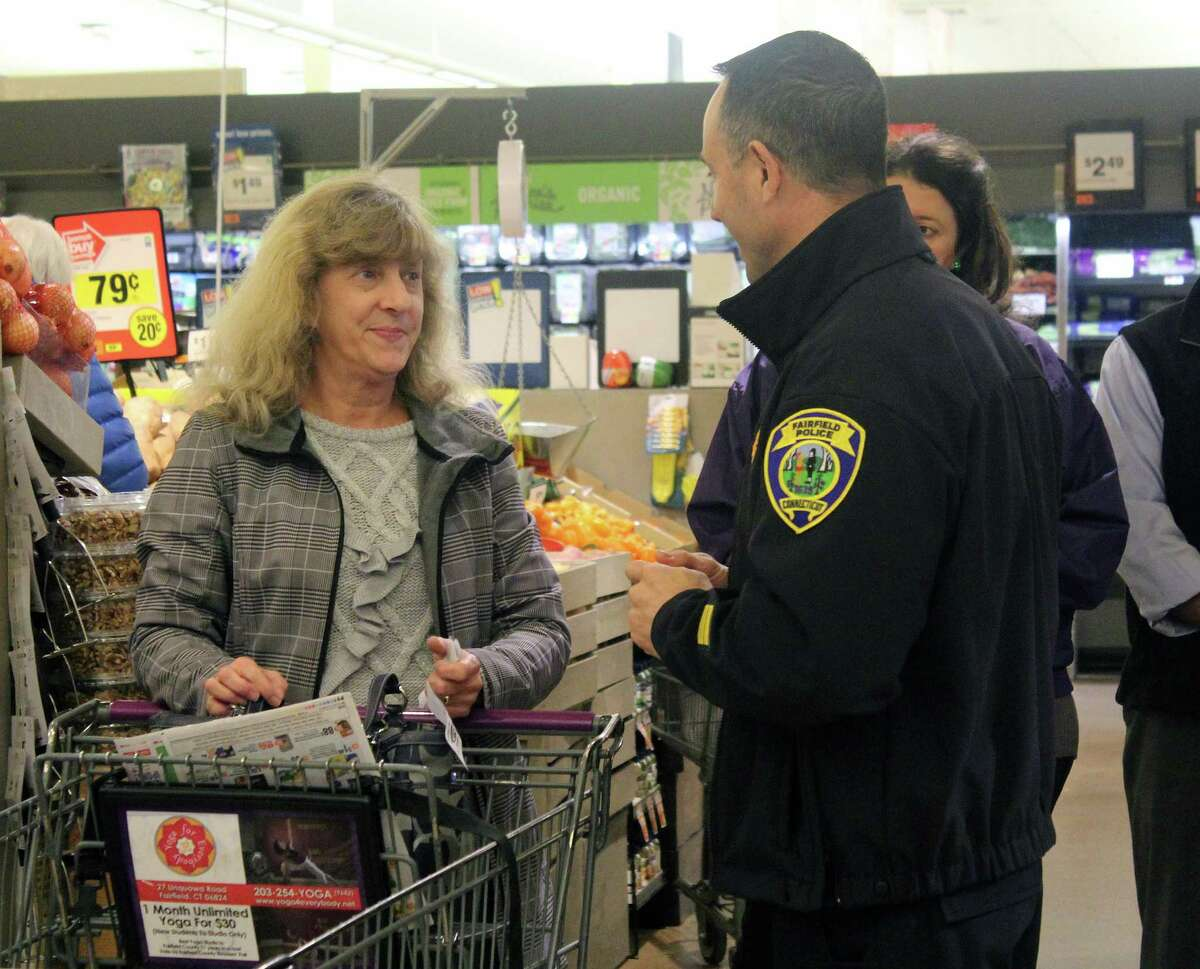 """Fairfield Police Lt. Robert Kalamaras gives grocery shoppers tips for protecting their belongings during a """"Purse Patrol"""" on Dec. 16, 2016 at a Stop & Shop in Fairfield, Conn."""